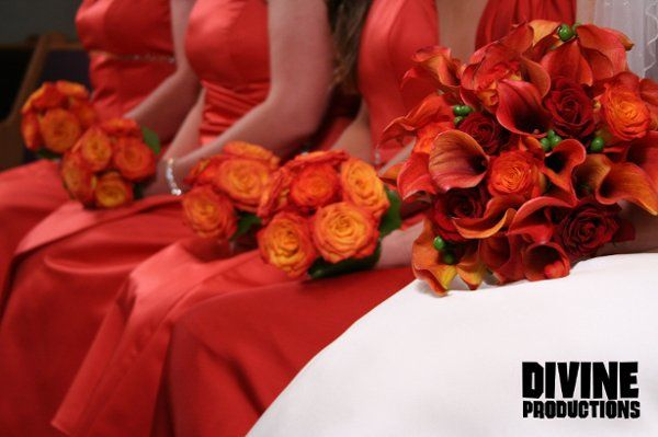 Tropical bridal bouquet of calla lilies, roses, and berries with bridesmaids' bouquets of circus...
