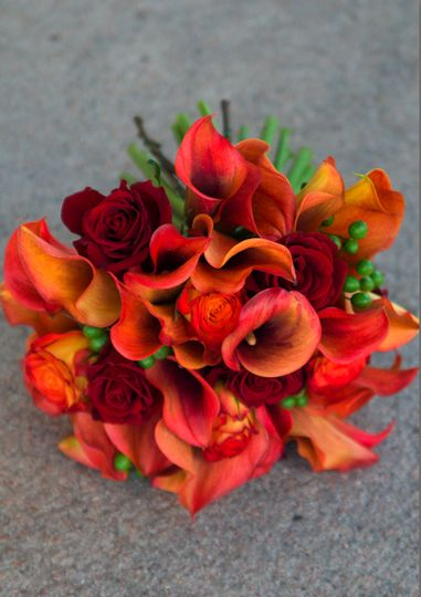 Calla lilies, two colors of roses and berries make up this warm bouquet.