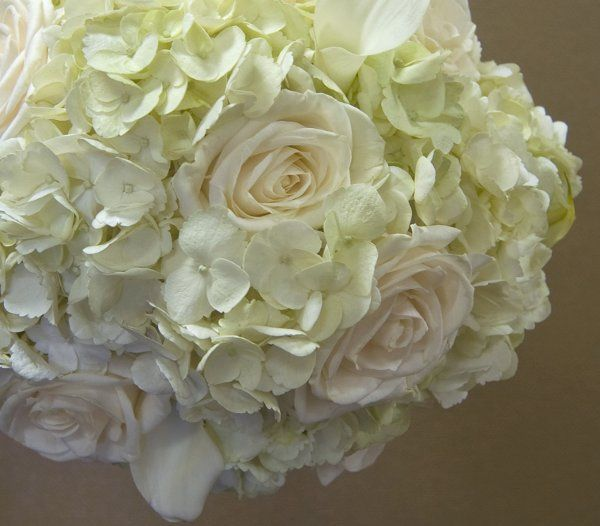 Monochromatic bouquet of calla lilies, hydrangea, and roses.