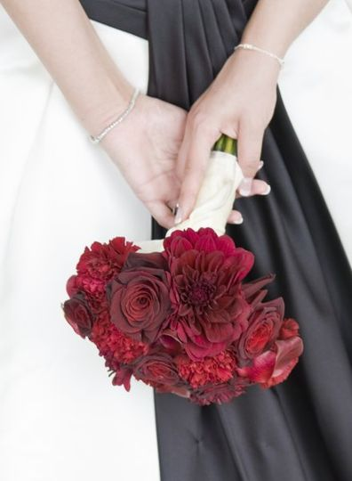 Striking red bouquet of roses, calla lilies, carnations, and dahlias.