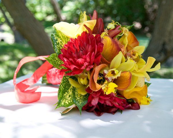 Bright bouquet of callas, orchids, dahlias, and  speckled foliage.