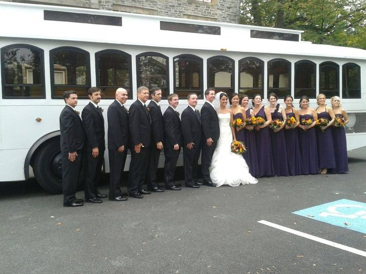 Newlyweds, bridesmaids, and groomsmen outside the trolley