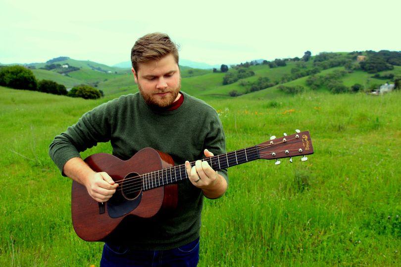 Playing guitar on a green hill