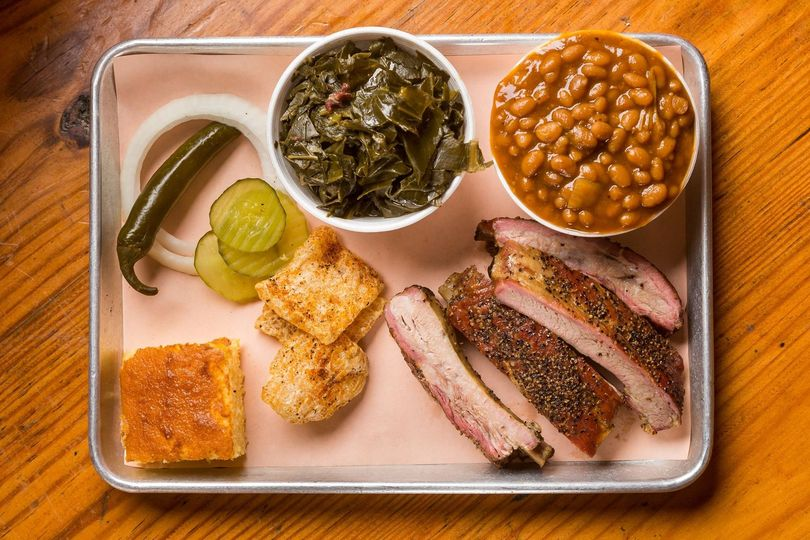 Pork spare ribs, collard greens, baked beans, pickles and peppers and a slice of cornbread