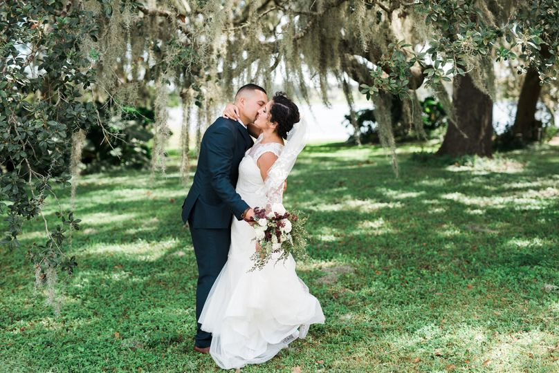Newlyweds kiss by the oak trees
