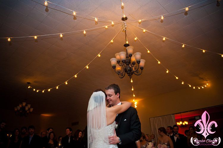 Newlyweds dancing underneath the lights