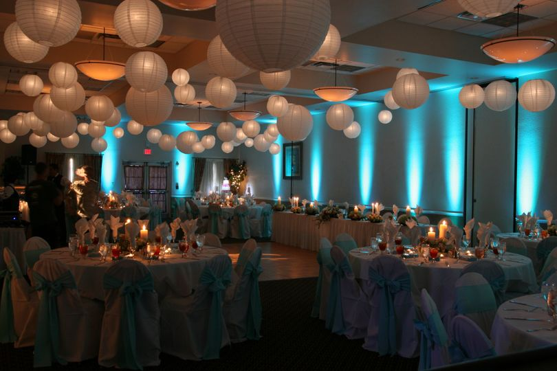 Elegant ballroom uplighting and lanterns hung from the ceiling.