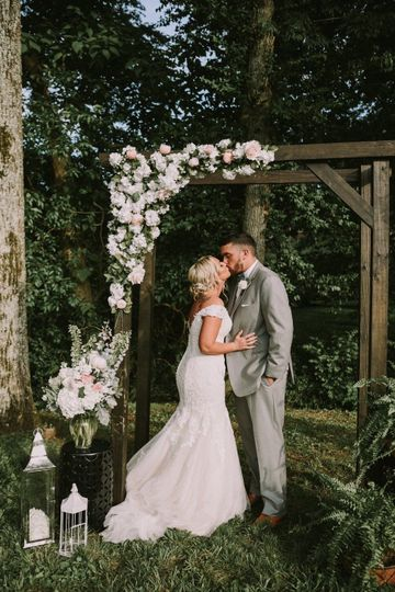 Couple kissing underneath a wedding arch