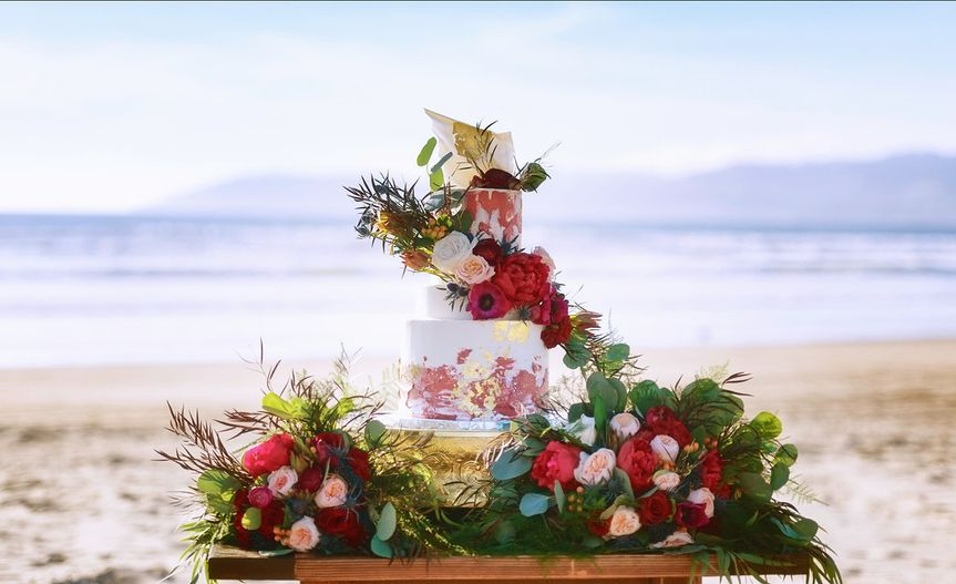 Wedding cake table and flowers by the beach