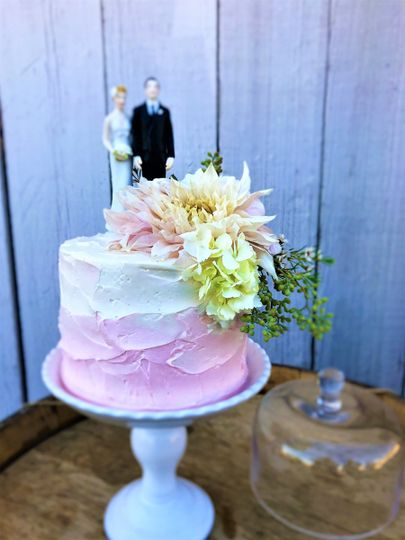 White and pink cake with figurines