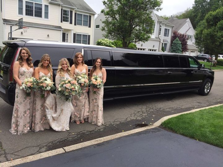 The perfect bridal party poses with our 12-passenger Cadillac Escalade.