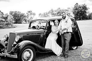 Bride and groom by their vintage car