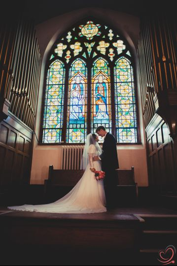 Couple standing under a stained glass window