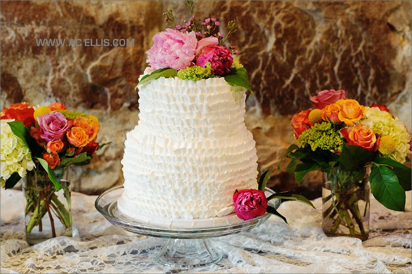 White wedding cake with pink flowers on top