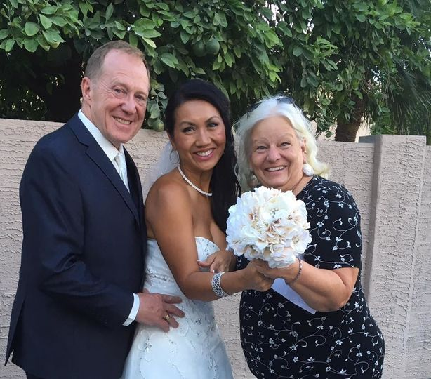 Happy officiant with newlyweds