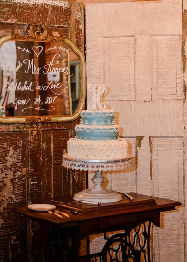 Wedding cake displayed on a vintage sewing machine base with vintage doors as a backdrop.