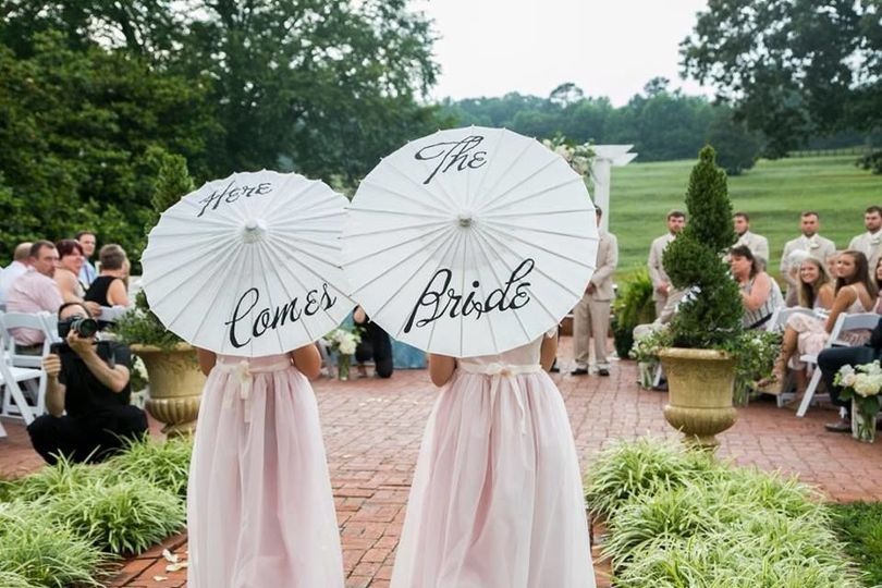 'Here Come the Bride' parasols set the tone for the brides arrival.