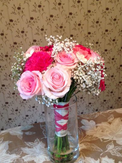 Shades of pink bridal bouquet using roses, carnations, and gypsophilia.  Ribbon is French braided on...