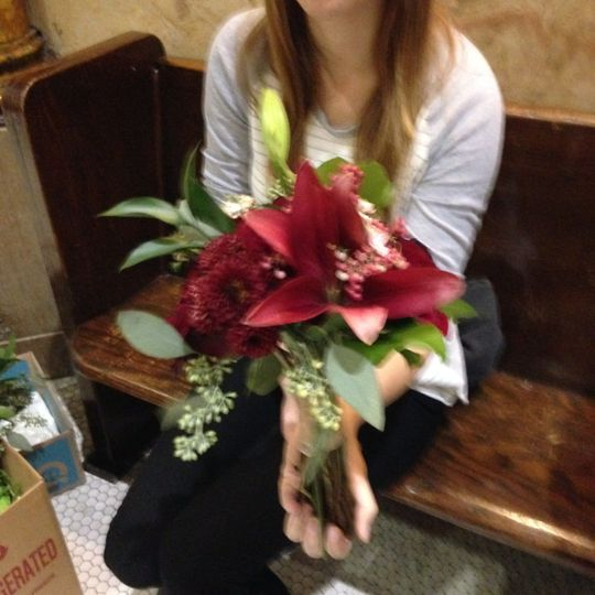 Wine colored lilies and greenery for a winter bridesmaid bouquet.