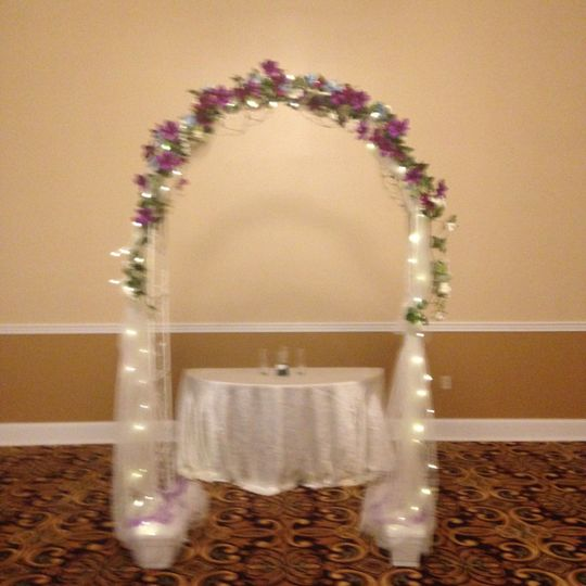 White metal garden arch with tulle, lights and permanent botanical flowers in the bridal colors.