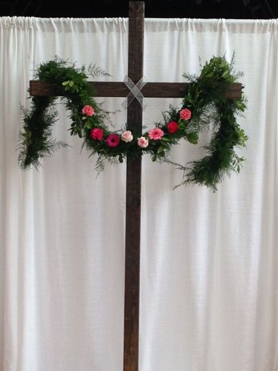 A fresh greenery garland and flowers adorn the cross to create an altar area for the ceremony.