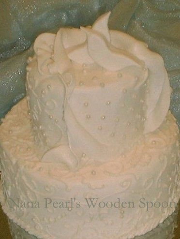 Elongated lacey swirls of icing and edible candy pearls adorn this fondant cake.  