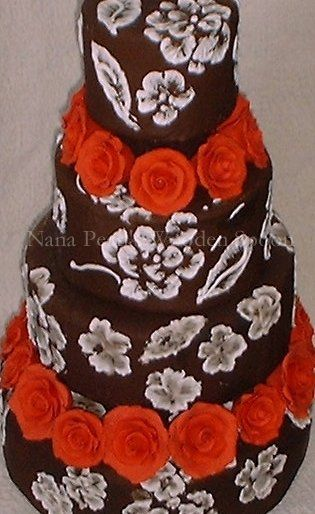 This dramatic cake features white floral brush embroidery over chocolate.  The cake is accented with...