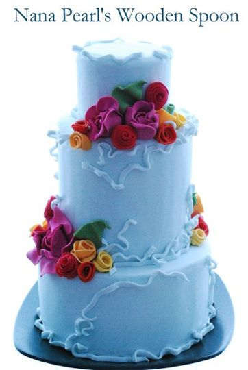 Vibrant and festive, this fondant wedding cake features wild roses, rosettes and ranunculus flowers....