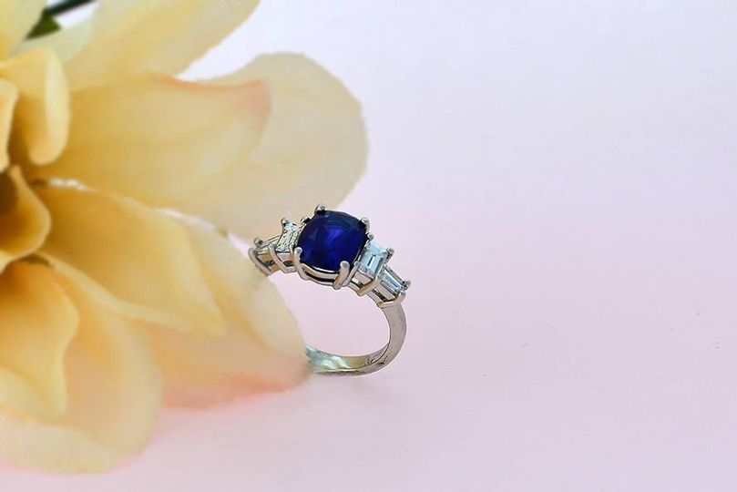 Sapphire flanked by emerald-cut diamonds