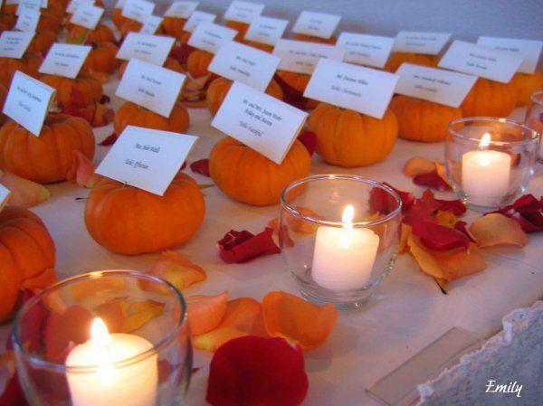 Creative placecard holders made of mini pumpkins set the fall harvest theme.