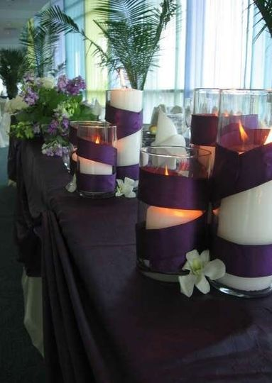 A head table design featuring deep purple linens and accents with shades of purple flowers, and soft...
