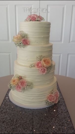 Four tier wedding cake with peach and pink flowers