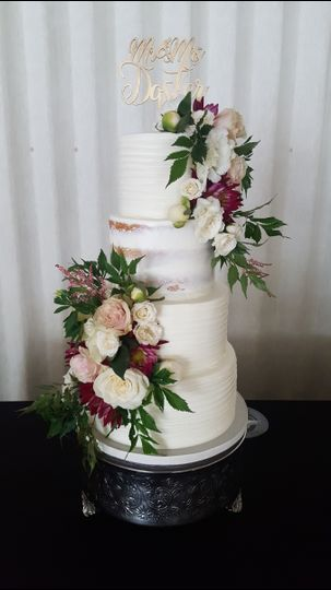 Four tier wedding cake with white and magenta flowers