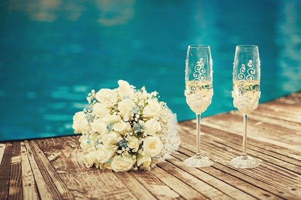 The simple elegance and romance captured from two glasses and a bouquet by the water