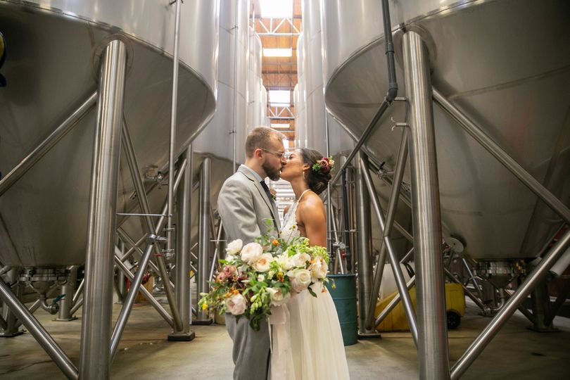 Newlyweds kiss by the brewery