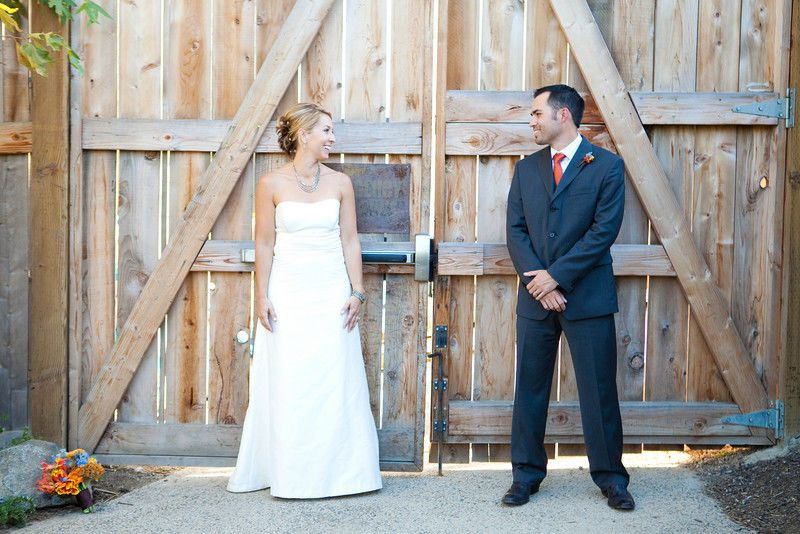 Newlyweds pose by the gate