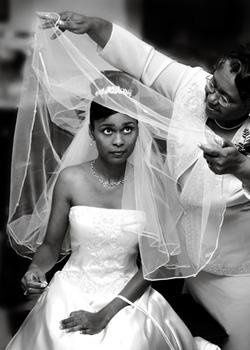 Bride's mother helps her with her veil as she gets ready