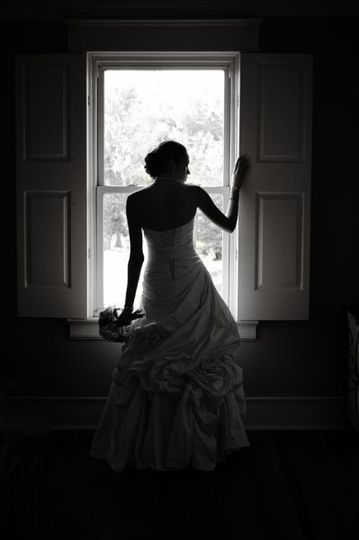 Silhouette of bride in window