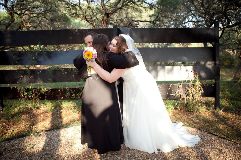 Reverend hugging the newlyweds