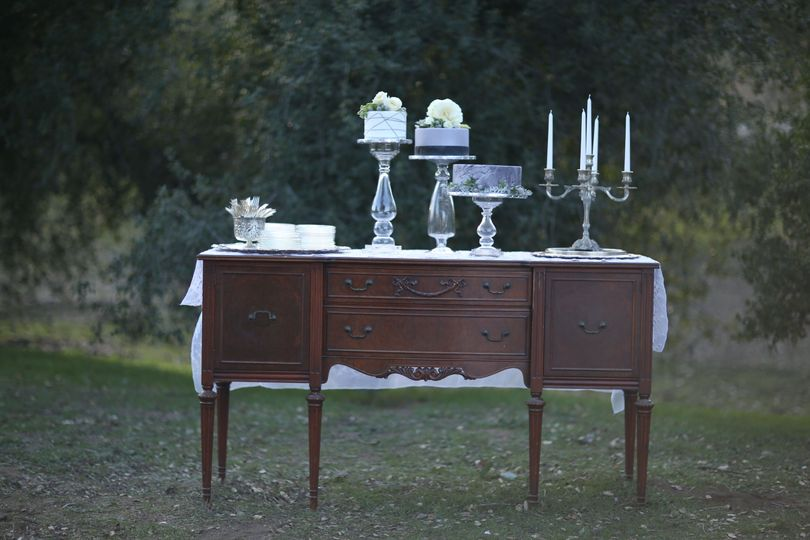 Mahogany buffet with silver candlesticks and cake plates.