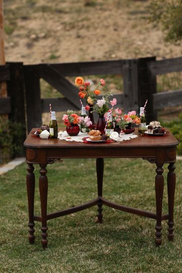 Vintage dining table with ruby glass vases and vintage table cloth.