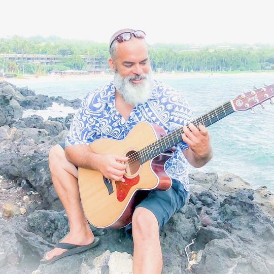 Playing the guitar by the beach