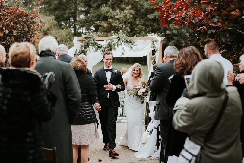 bride and groom down aisle with draped arbor 51 1022739 1573246508