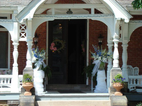White and blue arrangements featuring delphiniums grace the front porch of Mansion View.