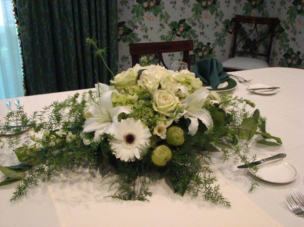 Elegant white and cream arrangement designed with white gerbera and stargazer lilies, creamy roses...