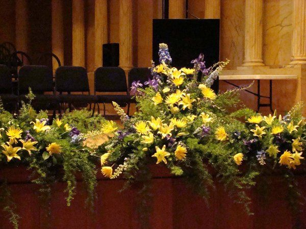 Blue delphinium, yellow lilies and carnations and cascades of springeri.