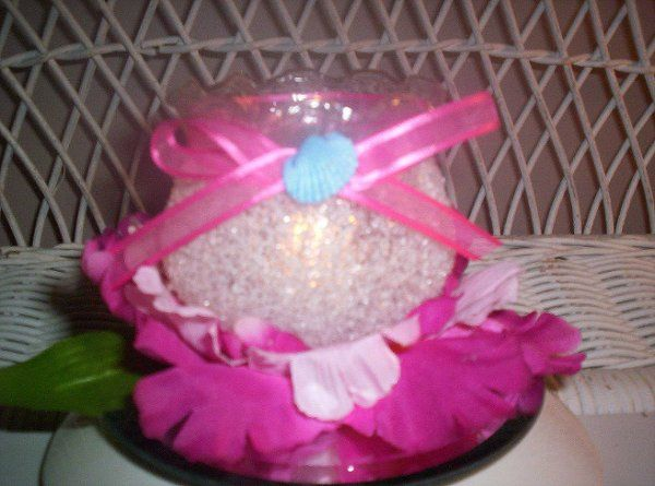 "3"" x 3"" fluted-edge container nestled in magenta orchid petals with hand-tied sheer ribbon and..."