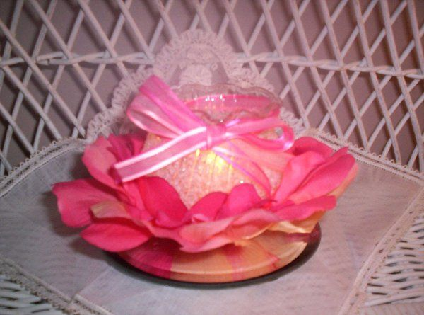 "3"" x 3"" container nestled in multi-shaded pink rose petals and a hand-tied coodinated sheer ribbon."