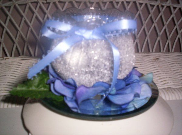 """3"""" X 3"""" fluted-edge container nestled in blue Hydrangea petals and a hand-tied matching ribbon."""