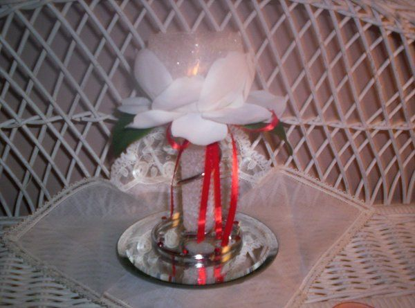 """6 """" wire-wrapped candle holder nestled in Magnolia petals and a hand-tied ribbon."""